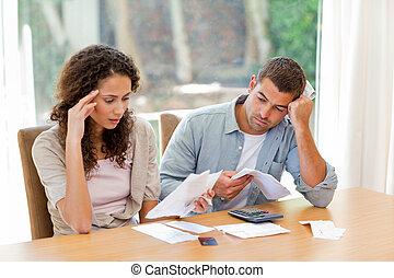 Ein junges Paar berechnet seine Hausrechnungen