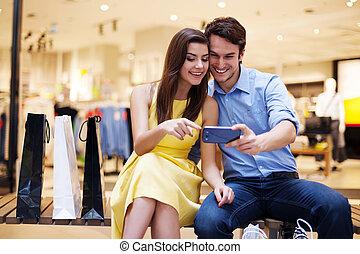 Ein lächelndes junges Paar, das auf Handy schaut