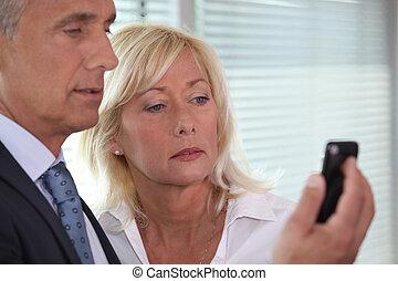 Ein Mann, der Frauen Handy zeigt