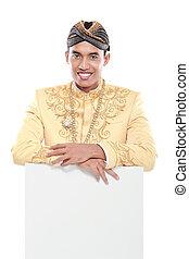 Ein Mann, der traditionelles Kleid aus Java trägt, mit leerem Brett