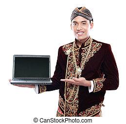 Ein Mann, der traditionelles Kleid von Java trägt und Laptop hält