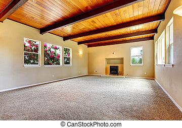 Ein neues leeres Wohnzimmer mit Holzdecke und Kamin.