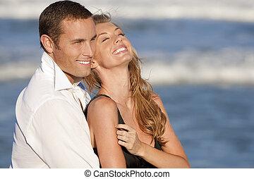 Ein Paar, das in romantischer Umarmung am Strand lacht