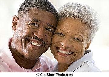 Ein Paar entspannt sich drinnen und lächelt
