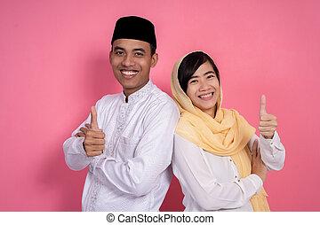 Ein paar Moslem-Asianer, die Daumen nach oben zeigen.