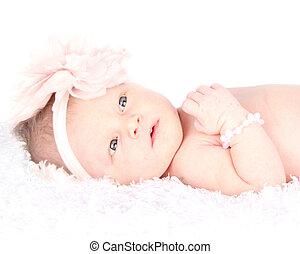 Ein waches Neugeborenes, das auf einer Decke liegt