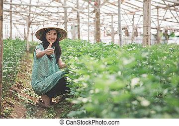 Ein weiblicher Farmer, der einen Daumen nach oben zeigt.