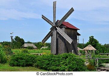 Eine alte Windmühle, ein dekorativer Storch in einem Nest.