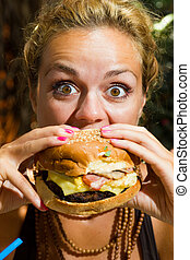 Eine Frau, die einen Cheeseburger isst