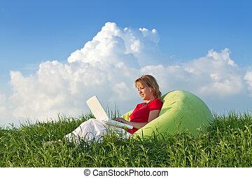 Eine Frau mit einem Laptop draußen