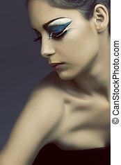 Eine Frau mit türkisfarbenem Augenschminke