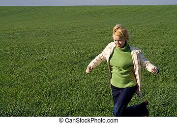 Eine Frau rast durchs Frühlingsfeld