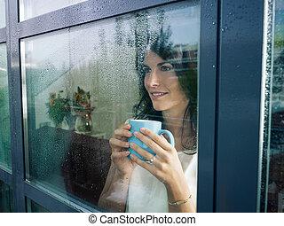 Eine Frau starrt aufs Fenster