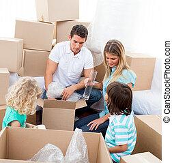 Eine glückliche Familie, die Kisten packt, während sie umzieht