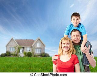 Eine glückliche Familie in der Nähe eines neuen Hauses.