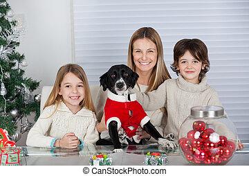 Eine glückliche Familie mit Hund zu Weihnachten