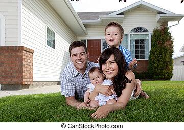 Eine glückliche vierköpfige Familie, die auf dem Rasen liegt
