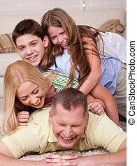 Eine glückliche vierköpfige Familie, die im Bett Spaß hat