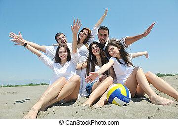 Eine Gruppe glücklicher junger Menschen, die am Strand Spaß haben