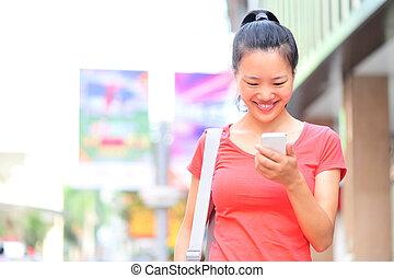 Eine junge Asiatin mit einem Smartphone.