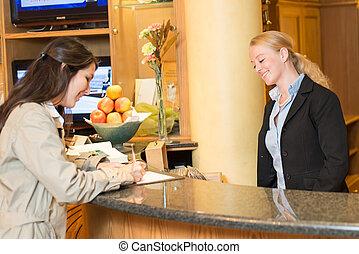 Eine junge Frau am Hotelempfang