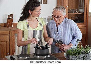 Eine junge Frau, die für eine ältere Dame kocht