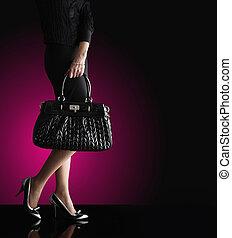 Eine modische Frau mit einer schwarzen Tasche, Modefoto