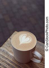 Eine Tasse Kaffee auf dem Holztisch.