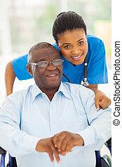 Elderly afrikanischer amerikanischer Mann und sorgend junger Pfleger.