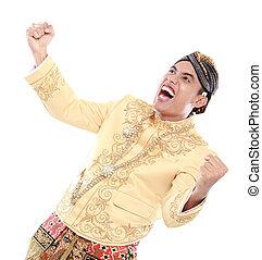Erregter Mann, der traditionell Java trägt und den Erfolg feiert