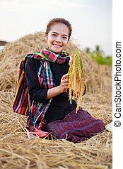 Farmer-Frau, die einen Reis mit Stroh im Feld hält.