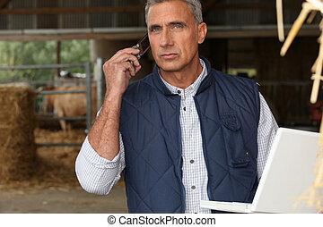 Farmer mit Handy und Laptop.