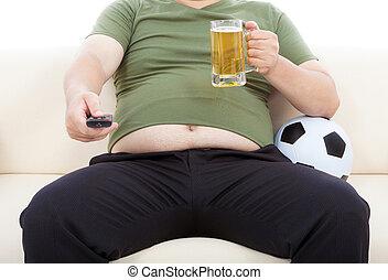 Fetter Mann trinkt Bier und sitzt auf dem Sofa, um fernzusehen.