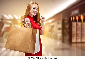 Fröhliche chinesische Frau mit traditionellen Kleidern mit Einkaufstaschen