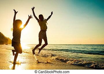 Fröhliche Kinder, die bei Sonnenaufgang am Strand spielen.