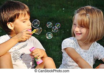 Fröhliche, süße Kinder, die mit Blasen spielen