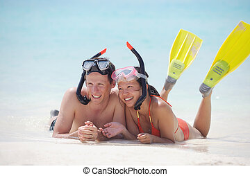 Fröhliches junges Paar, viel Spaß am Strand
