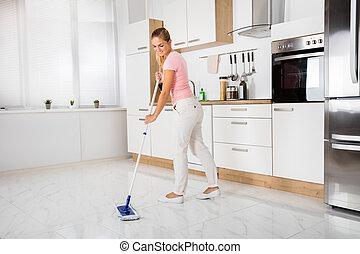 Frau mit Mopp steht in der Küche.