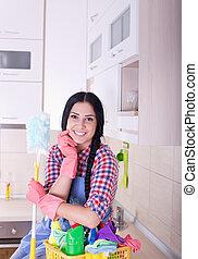 Frau mit Reinigungsmitteln in der Küche.