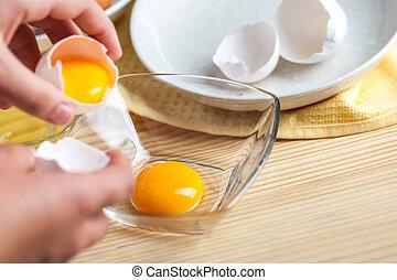Frauen Hände brechen ein Ei, um Eiweiß und Eigelb zu trennen, Eierschalen im Hintergrund.