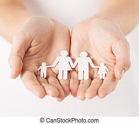 Frauenhände mit Papiermännerfamilie