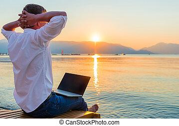 Freizeitunternehmer. Mann mit Laptop am Morgen auf dem