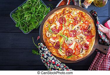 Frische italienische Pizza mit Hühnerfilet, Pilzen, Schinken, Salami, Tomaten, Käse auf einem schwarzen Hintergrund in den Händen. Italienisches Essen.