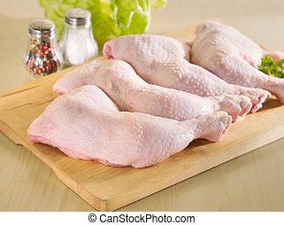 Frische rohe Hühnerbeine auf dem Küchenbrett