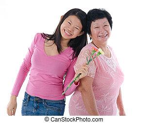 Frohe Asiatische Mutter und Tochter mit Nelkenblume mit isoliertem weißen Hintergrund