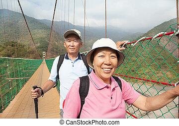 Frohes asiatisches Senior Paar, das auf der Brücke im Naturpark spazieren geht.