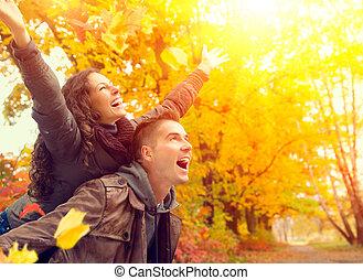 Frohes Paar im Herbstpark. Fallen. Familie hat Spaß draußen