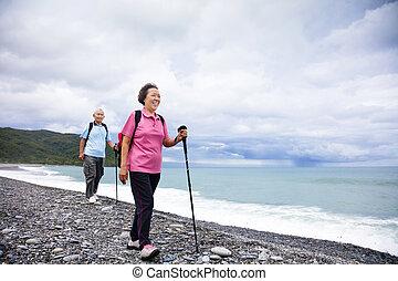 Frohes Senior Paar Wandern am Strand.