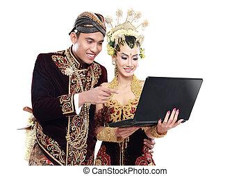 Frohes traditionelles japanisches Hochzeitspaar mit Laptop