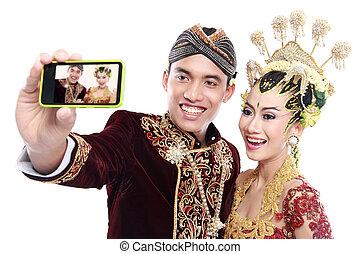 Frohes traditionelles Java-Hochzeitspaar mit Handy